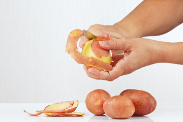 Female hands peeling potatoes with a knife