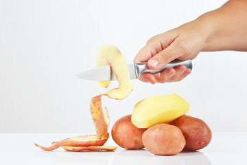 Female hands peeling fresh potatoes with a knife