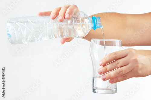 Female hand pour fresh water into a glass from bottle