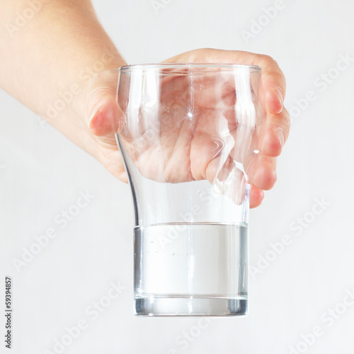 Female hand holding a glass of fresh water