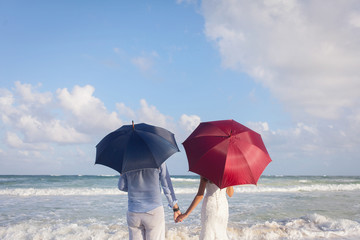 The couple of newly married stand on the beach with umbrellas