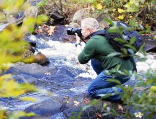 Male photographer taking photos in a waterfall in the Fall