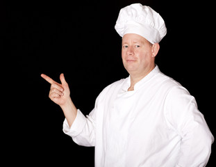 Male chef pointing on isolated black background