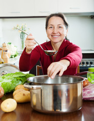 mature woman adding seasoning into lent diet soup