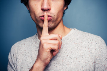 Young man gesturing hush with finger on lips