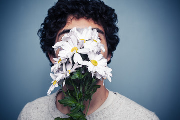 Young man hiding behind flowers