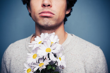 Sad and rejected man with a bouquet of flowers