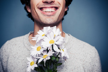 Happy young man with flowers