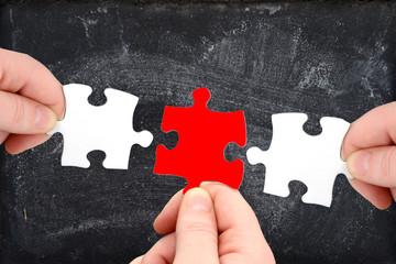 Drei Puzzleteile und Tafel mit Finger