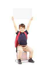 Happy schoolboy holding a panel above his head, seated on books