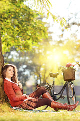 Young beautiful female with bicycle relaxing in a park