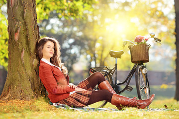 Young beautiful female with bicycle sitting on a grass