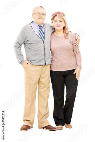 Full length portrait of a middle aged couple in a hug posing