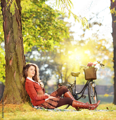 Young beautiful female with bicycle relaxing on a sunny day
