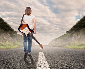 young musician woman walking on a road
