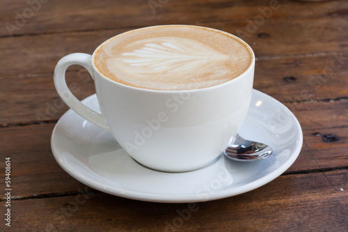 Latte art coffee over wooden background