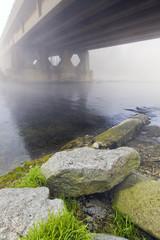 Winter riversides with bridge under the fog color image
