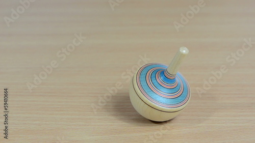 Hand try to spin whirligig peg-top toy on wooden background
