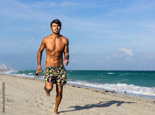 man running on the beach, in Miami beach