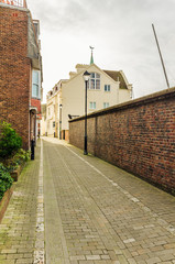 Narrow Cobbled Street Lined with a Brick Wall in Old Portsmouth
