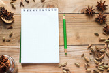 Notebook with green pencil and aromatic spices poster
