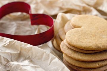 Heart shaped cookie cutter and a pile of brown gingerbread cooki