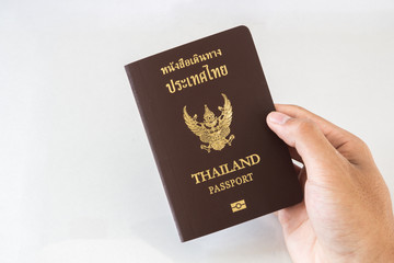 Hand holding an Thailand passport isolated on white background