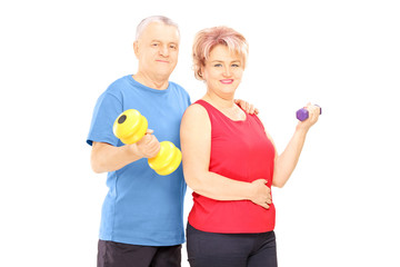 Mature man and woman holding dumbbells and looking at camera