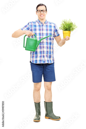 Male holding a watering can and a flower pot
