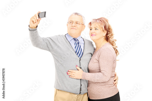 Happy mature man and woman taking pictures with phone