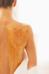 Closeup on young woman receiving honey spa therapy. rear view