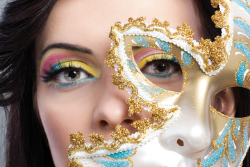 beautiful young woman with mysterious venetian mask close up
