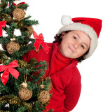 Funny boy with santa hat behind Christmas tree claus