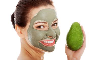 Beautiful spa woman in facial mask and avocado.