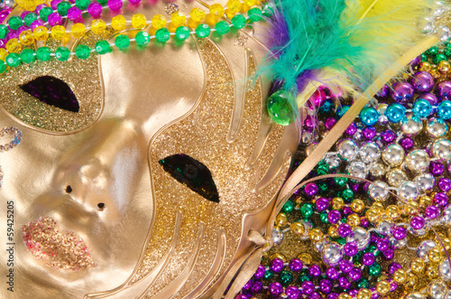 Festive Mardi Gras beads and a golden mask