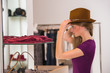 Beautiful woman shopping in clothing store trying on brown hat