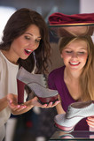 Two beautiful young girls choosing shoes at store