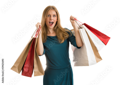 Young woman with shopping bags over white background screaming a