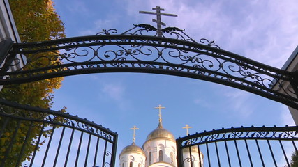 Church standing behind an intricate wrought iron gate