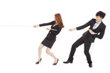 business man and woman playing tug of  war