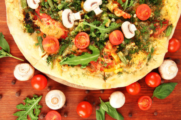Tasty vegetarian pizza and vegetables on wooden table