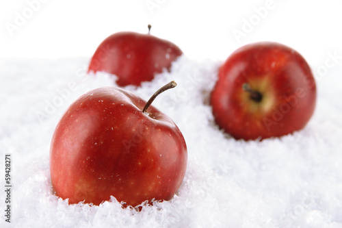 Red apples in snow isolated on white