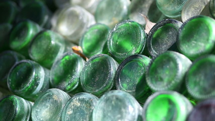 A dolly shot of stacked empty green glass bottles.