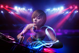 Fototapety Disc jockey girl playing music with light beam effects on stage