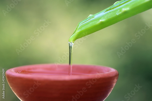 Falling aloe vera extract on a brown bowl