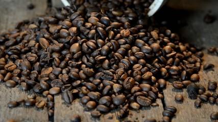 Ausgeschüttete Arabica Kaffeebohnen auf Holzuntergrund