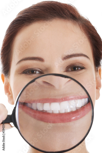 Beautiful young woman with magnifying glass on mouth.