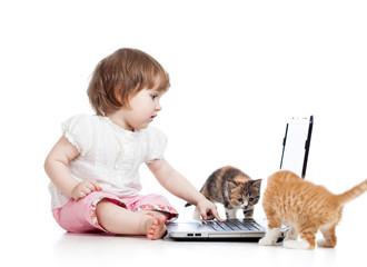 kid using a laptop and playing with kitten
