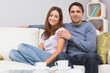 Relaxed couple sitting on sofa at home