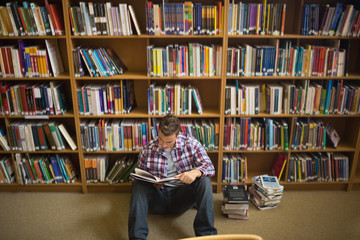 Concentrating young student sitting on library floor reading